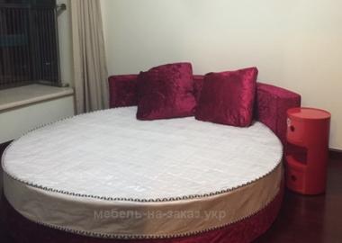 черная кровать круглой формы с подушками