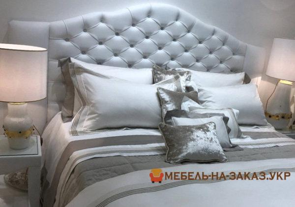 белое изголовье кровати с каретной стяжкой